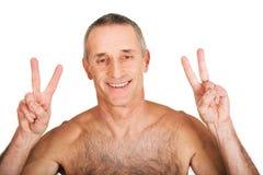 Homme sans chemise mûr avec le signe de victoire Images stock