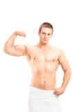 Homme sans chemise montrant son biceps Photos stock