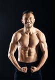 Homme sans chemise musculaire sexy sur le fond foncé Photo stock