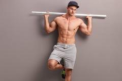 Homme sans chemise musculaire tenant un tuyau en métal photos libres de droits