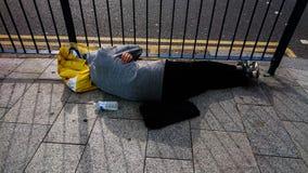 Homme sans foyer dormant dans la rue photo libre de droits