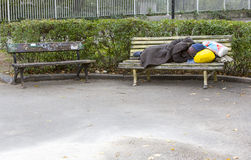 Homme sans foyer dormant sur un banc Image libre de droits