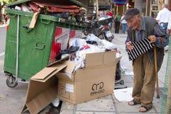 Homme sans foyer regardant dans un décharge image libre de droits