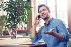 Homme satisfait parlant au téléphone portable Photo stock