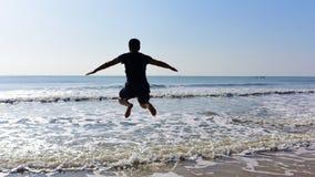 Homme sautant au-dessus de l'eau de mer Photos stock