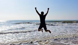 Homme sautant au-dessus de l'eau de mer et vagues dans le jour ensoleillé Photographie stock libre de droits