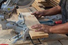 Homme sciant un conseil en bois photo stock