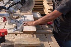 Homme sciant un conseil en bois photographie stock