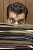 Homme scrutant par derrière la pile des dépliants. Images stock