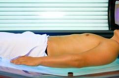 Homme se bronzant dans le solarium Image stock