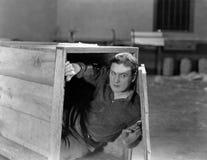 Homme se cachant dans la caisse en bois Image stock