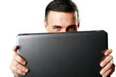 Homme se cachant derrière l'ordinateur portable Image libre de droits