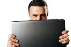 Homme se cachant derrière l'ordinateur portable Images libres de droits