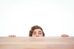 Homme se cachant derrière le bureau sur le fond blanc Photo libre de droits