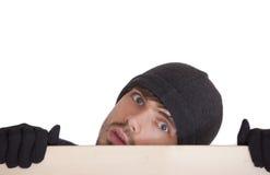 Homme se cachant derrière le panneau Images stock