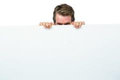 Homme se cachant derrière le panneau Photographie stock libre de droits