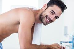 Homme se lavant le visage dans l'évier photographie stock libre de droits