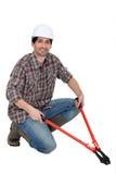 Homme se mettant à genoux avec des boulon-coupeurs Images libres de droits