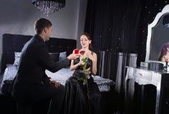 Homme se mettant à genoux en Front Girlfriend avec le cadeau de bijoux Photos stock