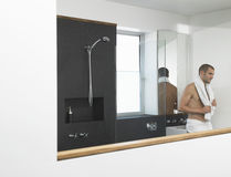 Homme se penchant contre l'évier dans la salle de bains Photo libre de droits