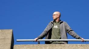 Homme se penchant sur la balustrade photo stock
