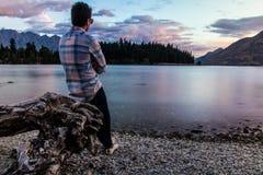 Homme se penchant sur le bois de flottage et la nature admirative photo libre de droits