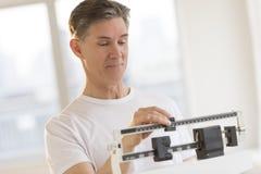 Homme se pesant sur l'échelle de contrepoids photographie stock