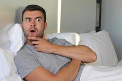 Homme se rappelant quelque chose dans le lit Image libre de droits