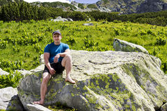 Homme se reposant après la hausse sur des montagnes Image libre de droits