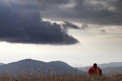 Homme se reposant aux montagnes Photographie stock libre de droits
