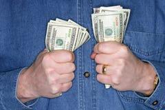 Homme se retenant en fonction sur l'argent comptant image stock