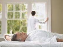Homme se situant dans le lit avec la femme se tenant à la fenêtre photo stock