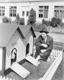 Homme se tapissant à côté de la maison de canard (toutes les personnes représentées ne sont pas plus long vivantes et aucun domai Image libre de droits
