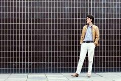 Homme se tenant à côté d'un mur Photographie stock