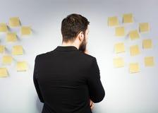 Homme se tenant à côté d'un mur avec des post-its Image stock