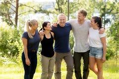 Homme se tenant avec des bras autour des amis dans la forêt Images stock