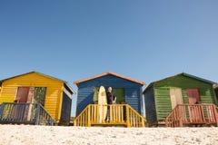 Homme se tenant avec la planche de surf à la hutte de plage Photos libres de droits