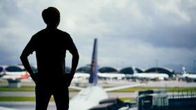 Homme se tenant avec la scène de silhouette à l'aéroport Image libre de droits