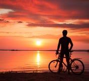 Homme se tenant avec un vélo au coucher du soleil Images stock