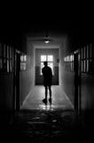 Homme se tenant dans le couloir sombre Photos stock
