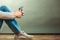 Homme se tenant dans le téléphone portable de mains Photographie stock libre de droits