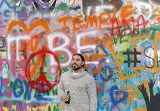 Homme se tenant devant le mur coloré de graffiti Image stock