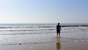Homme se tenant en mer avec des vagues Images stock