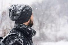 Homme se tenant en parc tandis que neige photographie stock libre de droits