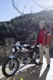 Homme se tenant près d'une motocyclette Photos libres de droits