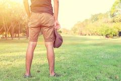 Homme se tenant sur l'herbe tenant un chapeau Image stock