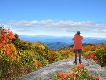 Homme se tenant sur la montagne prenant des photos Photo stock
