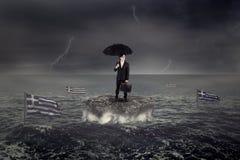 Homme se tenant sur la roche avec l'évier de drapeau de la Grèce sur la mer Images stock