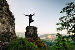 Homme se tenant sur le dessus de la montagne dans la pose de yoga Image libre de droits
