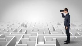 Homme se tenant sur un labyrinthe avec des jumelles image libre de droits